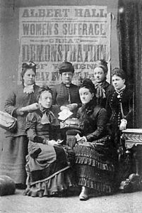 Undated. View shows six women in Victorian period dress from the suffrage movement in front of a poster declaring: 'Albert Hall, Sheffield, Women's Suffrage, Great Demonstration of Women'. Lady seated front right maybe Alice Cliff Scatcherd. Courtesy of www.leodis.net